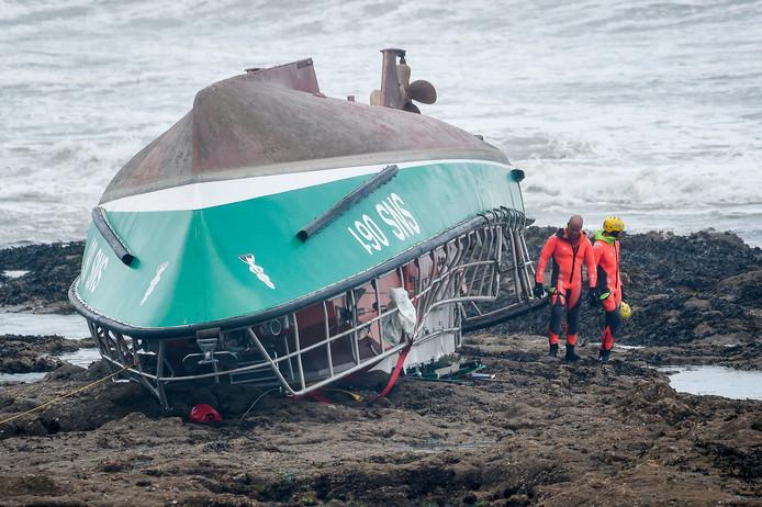 Teneergeslagen reddingswerkers bij de reddingsboot.