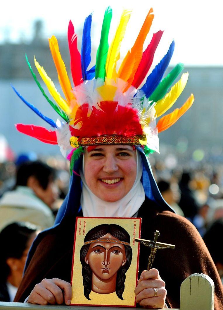 Een gelovige met een portret van Kateri Tekakwitha. Beeld afp