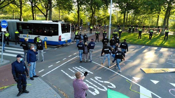 De eerste activisten worden door de politie weggehaald.