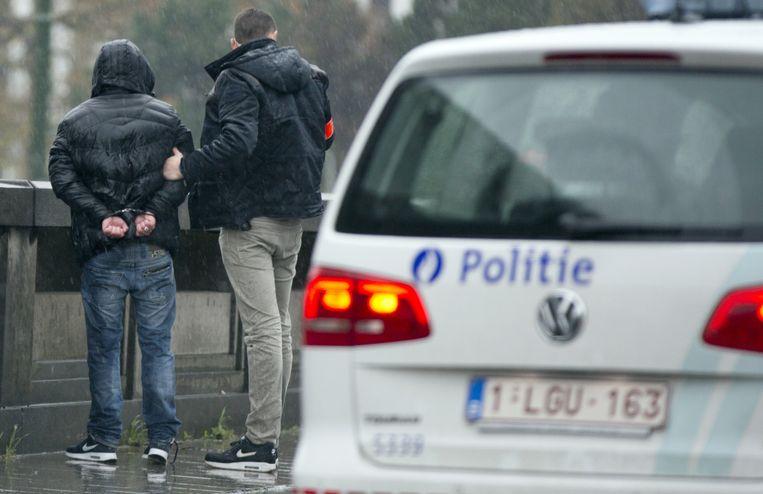 Een man wordt aangehouden en gefouilleerd in Brussel. Beeld ap