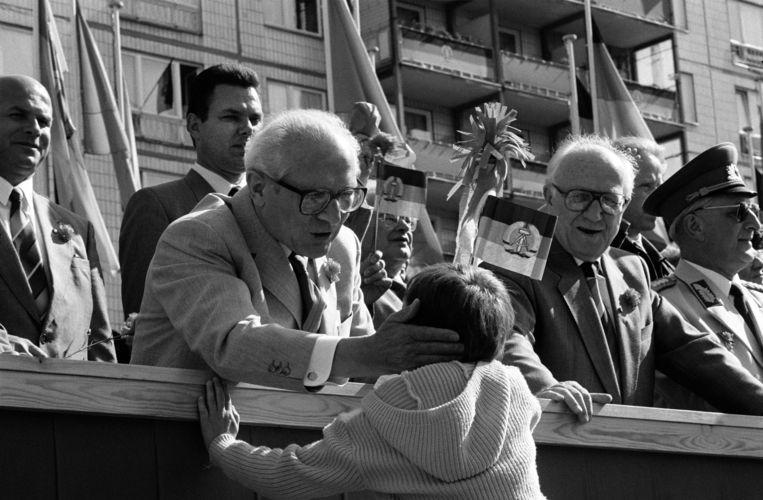 Erich Honecker houdt bij de 1-meiparade van 1989 een jongeling vast alsof het een reddingsboei betreft. Beeld Giribas Jose / HH