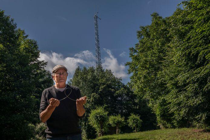 """Theo Nooijen met zijn wichelroede bij de mast aan de Lange Akker in Aarle-Rixtel: ,,Het is een natuurkundig verhaal dat klopt."""""""