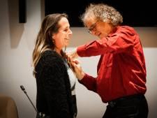 Brede glimlach voor vertrekkend raadslid Sandra Hol: echtgenoot spelt lintje bij haar op