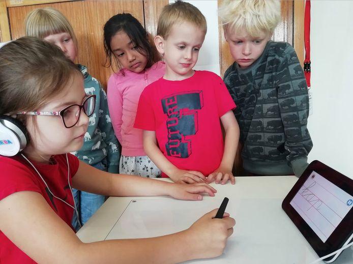 Enkele leerlingen demonstreren de schrijfrobot.