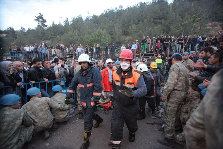 Reddingswerkers dragen een lichaam weg, terwijl de spanning aan de mijn te snijden is.