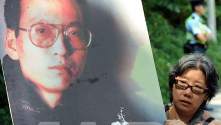 Een vrouw toont een spandoek met Liu Xiaobo. Beeld