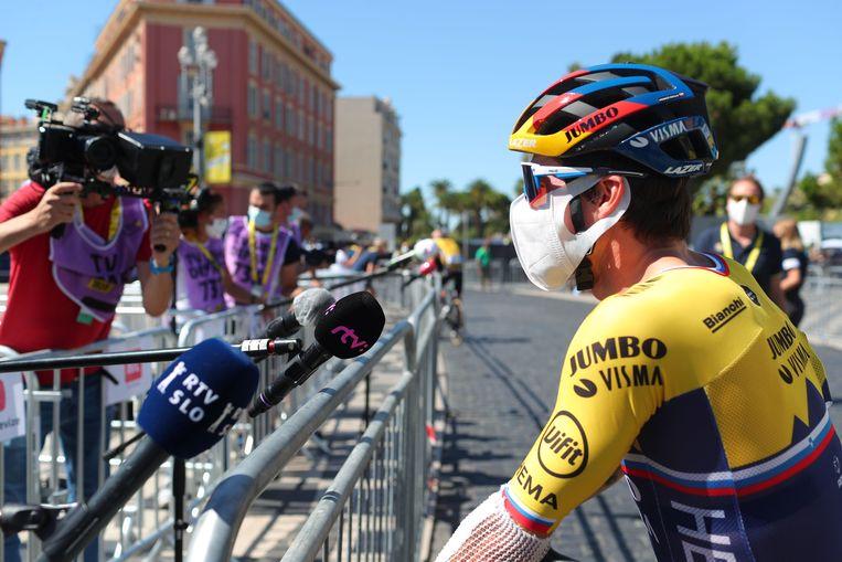 Jumbo-Vismarenner Primož Roglič staat de pers te woord voor de tweede etappe van de Tour. Er zijn forse beperkingen op interactie met journalisten ingesteld. Beeld AFP
