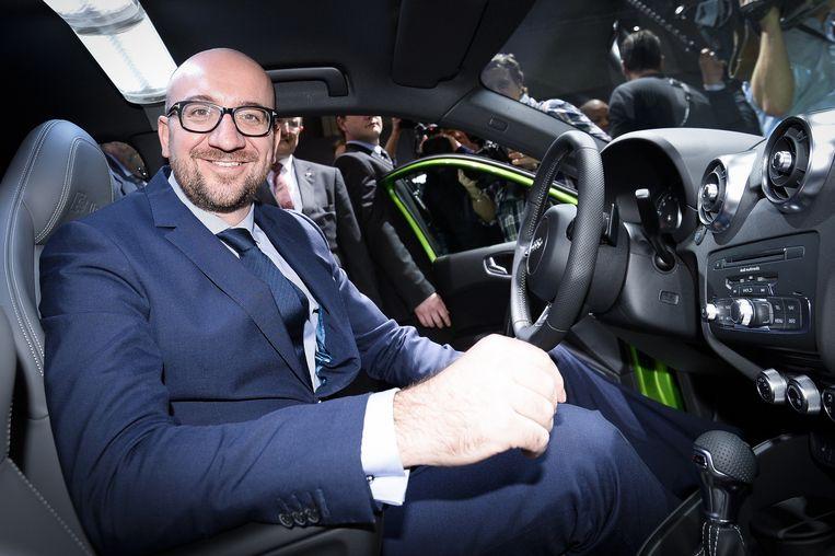 De Belgische premier Michel poseert in de nieuwe Audi A1 op een Brusselse autobeurs. Beeld belga