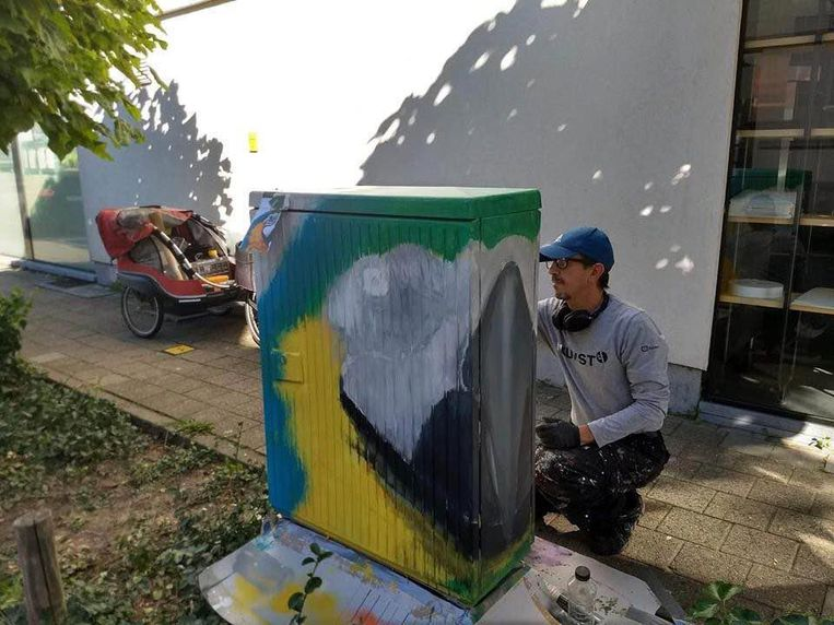 Een kunstenaar legt de laatste hand aan zijn afbeelding van een papegaai.