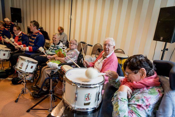 Bewoners van het eerste uur van de LosserHof, Maria Spanjer, Lies Engbers, Annie Niezink en Annie Lenferink, volgen in de feestweek een percussiesessie.