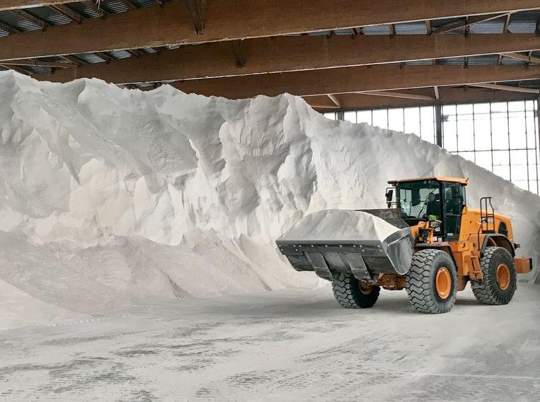 Een bulldozer schept een hoop zout van de bergen in de hallen van Willems.