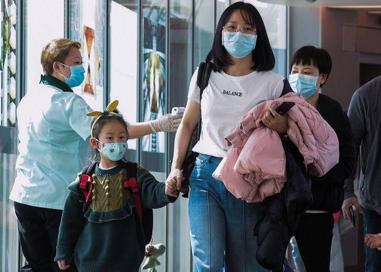 Passagiers uit China worden gescand op het Changi International Airport in Singapore. Beeld AFP