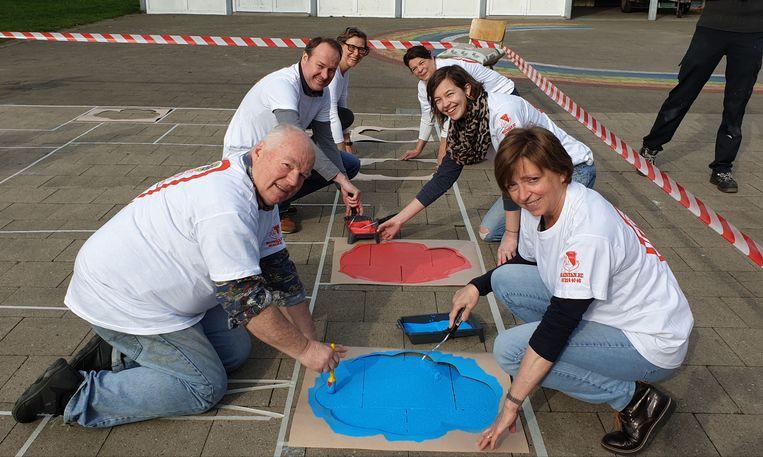 Leden van de Hartevrouwe schilderen op de speelplaats van de school Lentekind in Vlimmeren.