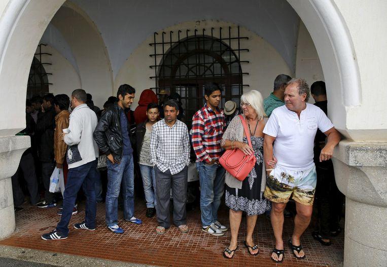 Een toeristenstel (rechts) schuilt samen met een groep migranten voor de regen bij een politiebureau op Kos. De vluchtelingen die aankomen op het Griekse eiland willen snel doorreizen, maar moeten soms een maand wachten op hun tijdelijke verblijfsvergunning. Behrakis/Reuters Beeld reuters