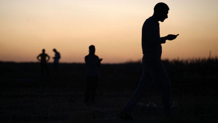Uit Irak gevluchte Yezidi's zoeken in het Turkse Sirnak naar een goed signaal voor hun smartphone. Beeld getty