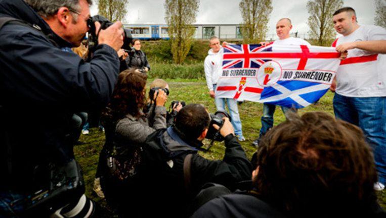 Leden van de English Defence League tonen zaterdag een vlag aan de media. © anp Beeld