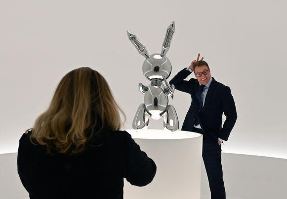 Een man poseert naast de stalen sculptuur 'Rabbit' van Jeff Koons.