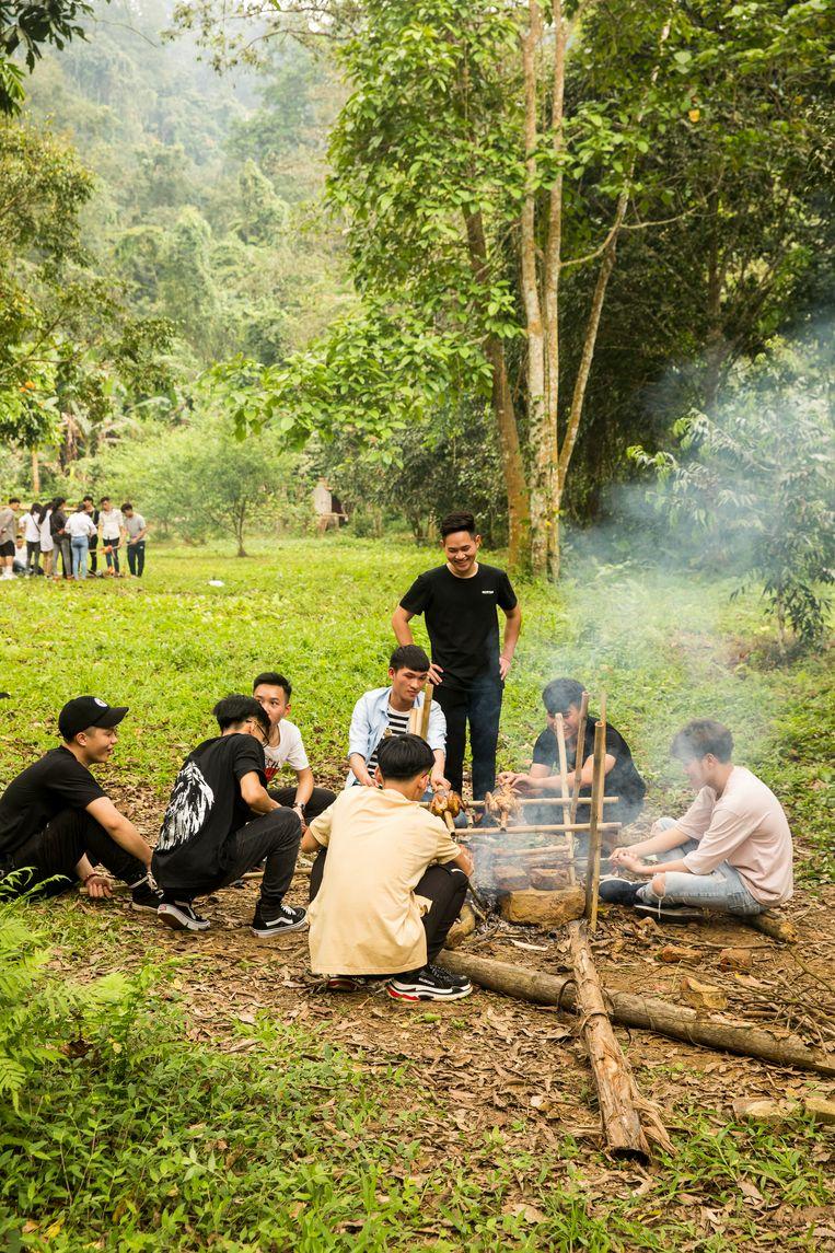 Tieners die een kippetje aan het braden zijn bij het Cuc Phuong National Park. Beeld Marie Wanders