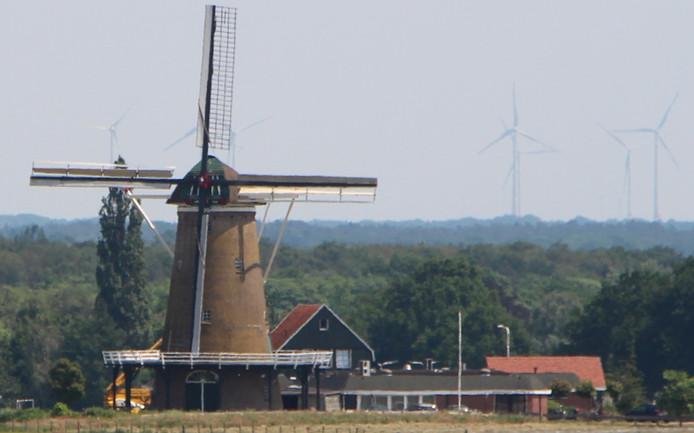 De Hollandsche Molen aan de Diepenheimseweg bij Neede, geflankeerd door moderne Duitse windmolens in Ottenstein (Ahaus).
