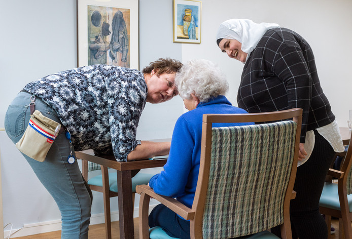 Deelneemster Sahar Asmail (rechts) en haar begeleidster Riekie Timmer in gesprek met één van bewoners van De Speulbrink.