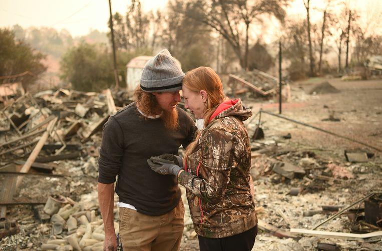 Tussen de resten van hun huis vinden Ryan Spainhower en zijn vrouw Kimberly een muntje dat speciaal voor hun huwelijk werd geslagen. Het is ondanks de hitte van het vuur niet gesmolten. Josh Edelson / AFP Beeld AFP
