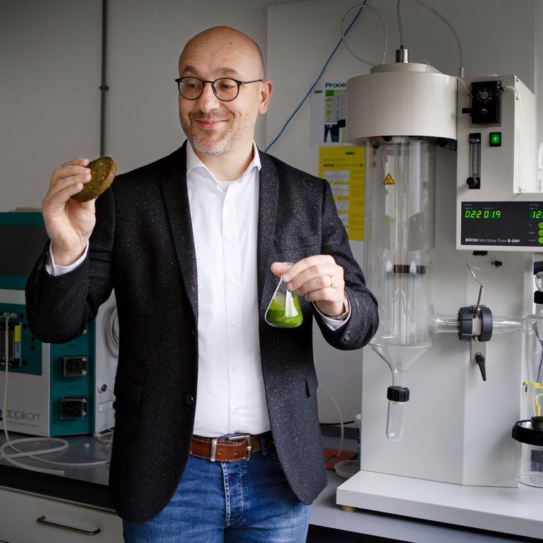 Marcel Oogink van Duplaco met in zijn rechterhand de algen-quinoa-burger en in zijn linker de algendrap.  Beeld null