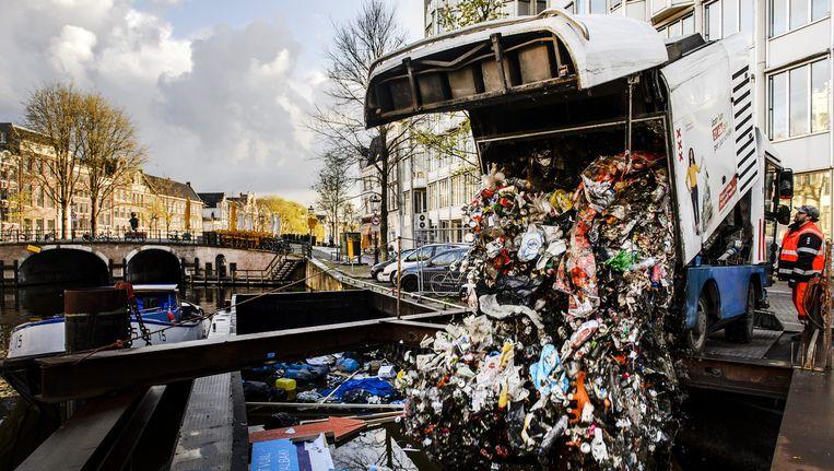 Schoonmaakploegen storten afval in een grote stortschuit aan het Singel. Beeld anp