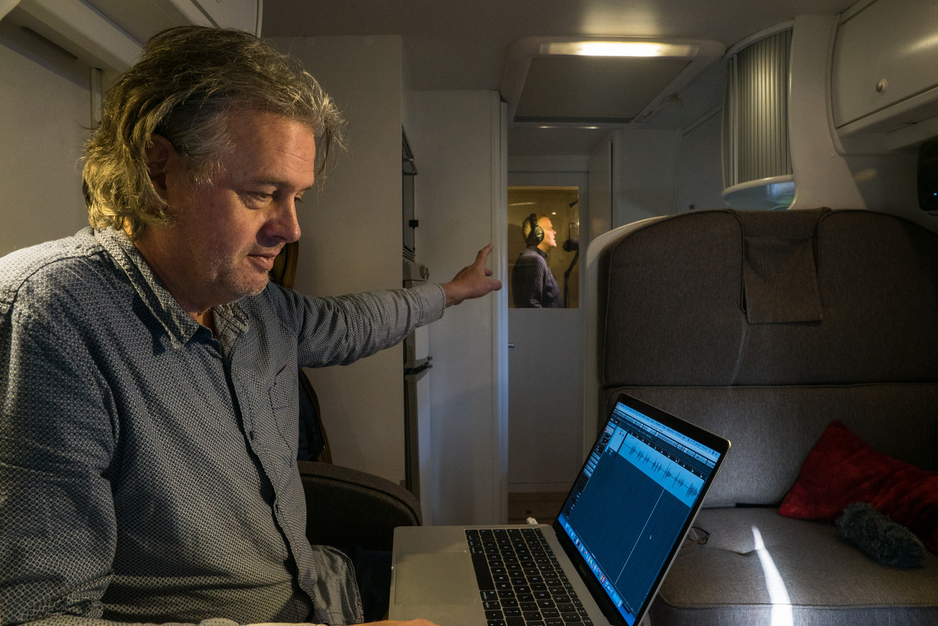Ron van Dulmen geeft aanwijzingen in De Stembus terwijl verslaggever Gert Kramer in de spreekcel een commercial inspreekt voor De Stentor.