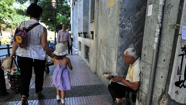Een oude man bedelt op een straat in Athene. Beeld null