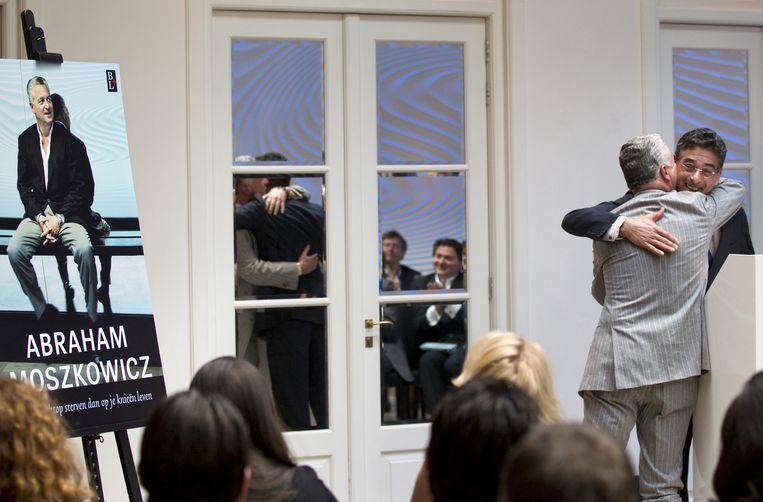 Spong omhelst Bram Moszkowicz tijdens de presentatie in 2012 van diens boek 'Abraham Moszkowicz, Strafpleiter'. Beeld anp
