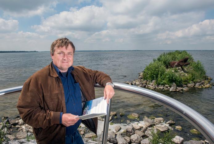 Peter Bosman uit Bergen heeft een vaargids geschreven over de Randmeren. Met zijn boek staat hij op het uiterste puntje van het Strandeiland in Harderwijk. Achter hem het Wolderwijd, dat onderdeel uitmaakt van de Randmeren.