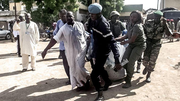 Een slachtoffer wordt weggedragen van de plek in de Kameroense stad Maroua, waar op 22 juli een dubbele zelfmoordaanslag plaatsvond. Beeld AFP