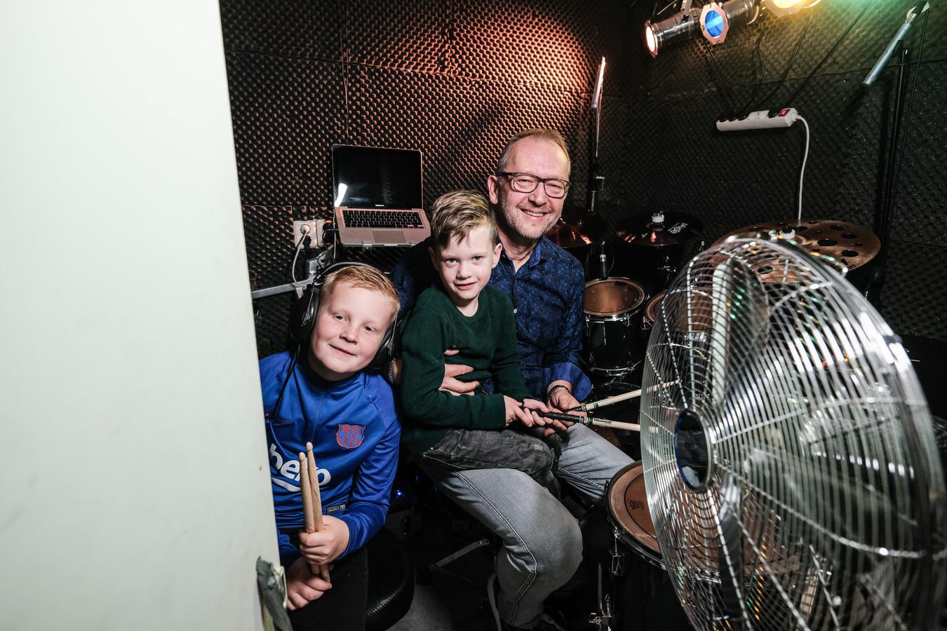 Opa John van Beem met zijn kleinkinderen in de drumkamer.