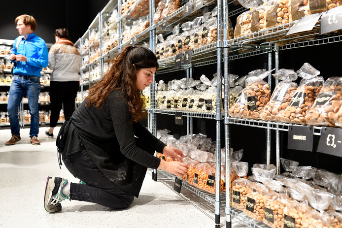 Het is druk in de pepernotenfabriek. Medewerkster Gina vult de schappen aan.
