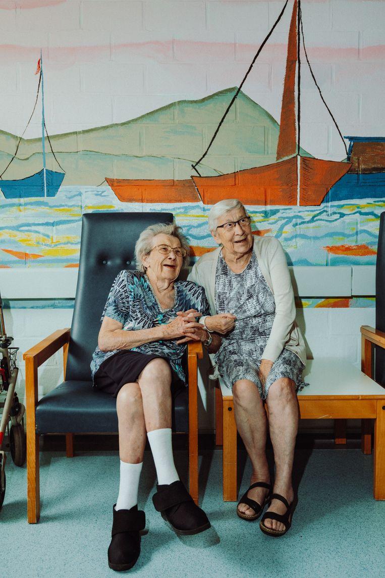 Vriendinnen Jeanne De Cock en Lucy Moens aan de babbel in het rusthuis in Lebbeke.  Beeld Illias Teirlinck