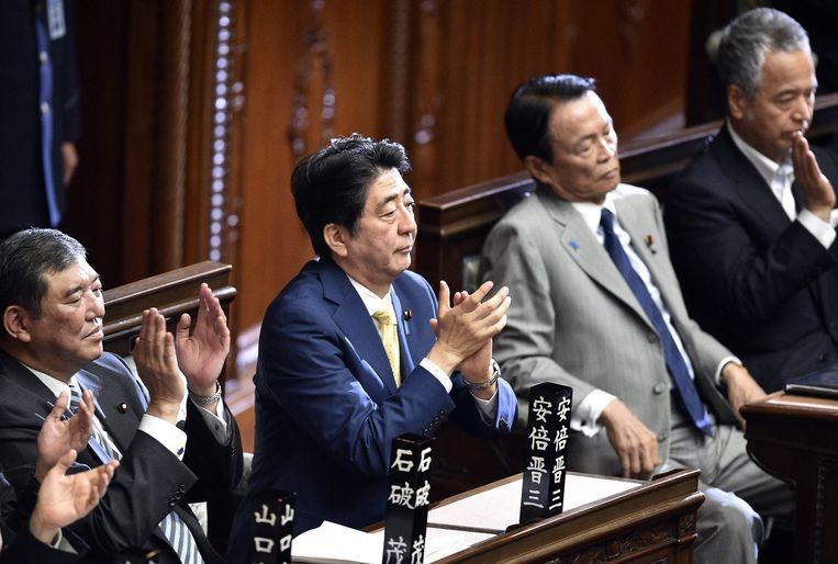 Premier Abe klapt nadat de wetswijziging is aangenomen in de Tweede Kamer. Beeld epa