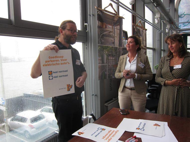 Christianne van der Wal (midden) en Marja Ruigrok bedenken slogans met Joris van Greenpeace Beeld