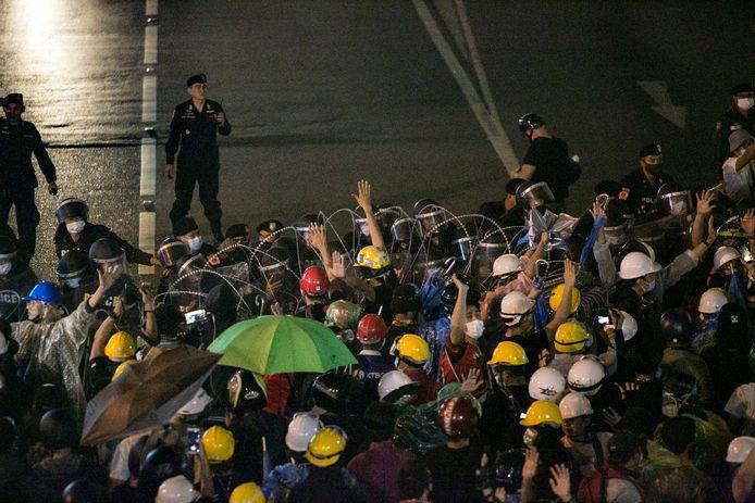 Demonstranten worden tegengehouden door een politiebarricade in Bangkok.
