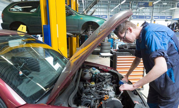 Een automonteur repareert een auto. Beeld anp