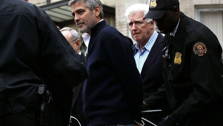 George Clooney wordt in de boeien geslagen. Beeld getty