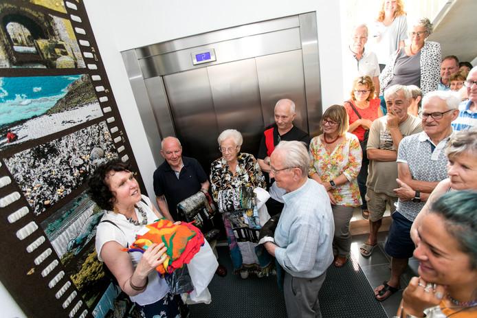 De drie oudste bewoners van de Woonbedrijf-woningen aan Boulevard Zuid Eindhoven onthullen het eerste wandkleed dat Mariëlle van den Bergh (linksvoor) maakte van hun herinneringen. Linksachter Jan van den Heuvel, met naast zich Lenie en Henk van de Wiel.