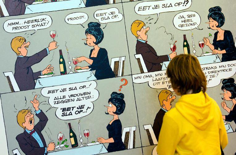Een vrouw kijkt naar tekeningen van Jan Kruis in het Stripmuseum in Groningen. Beeld anp