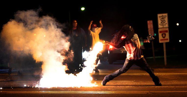 Een demonstrant gooit een traangasgranaat terug naar de oproerpolitie in Ferguson Beeld ap