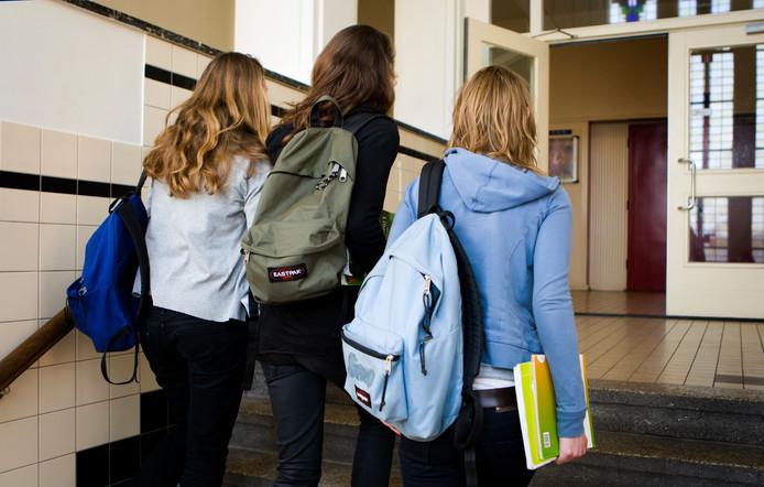 Ter illustratie.Scholieren met schooltassen.