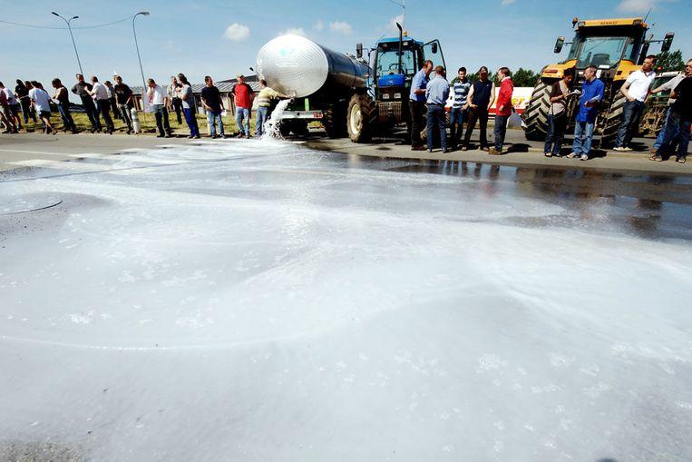 Franse en Belgische boeren dumpen melk en water op een straat in het noord-Franse Bettignies. Ze vragen aandacht voor de dalende melkprijzen. (AFP) Beeld