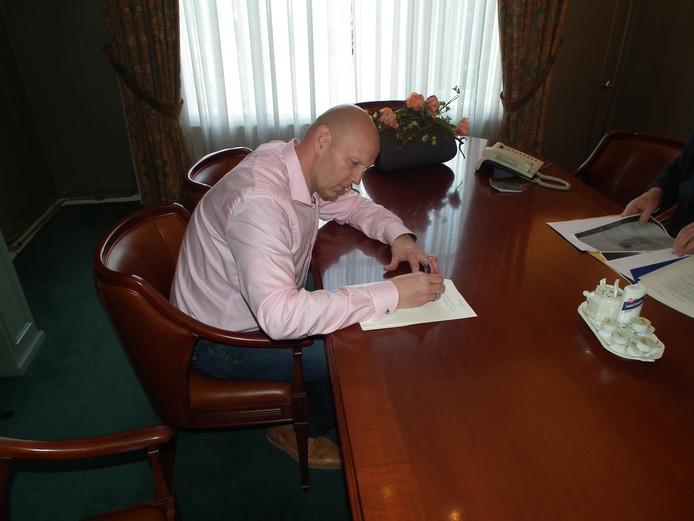 Van den Essenburg tekent het contract bij de notaris.