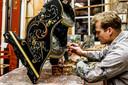 Titus Stallmann legt de laatste hand aan een meubelstuk bij Roosje Hindeloopen