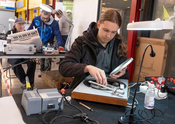 Owen Vader aan het werk aan een platenspeler bij het Repair Café in Middelburg.