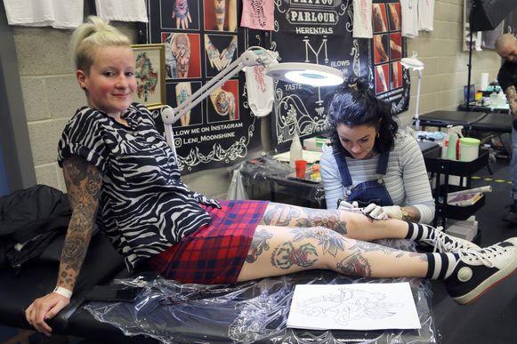Anneleen Moorkens laat een tatttoo zetten op haar onderbeen.