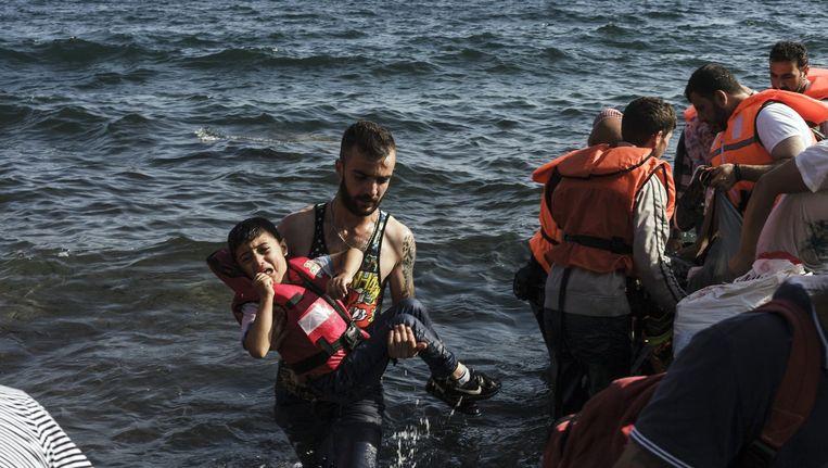 Een Syrische vluchteling draagt een kind het strand op van Lesbos. Beeld afp
